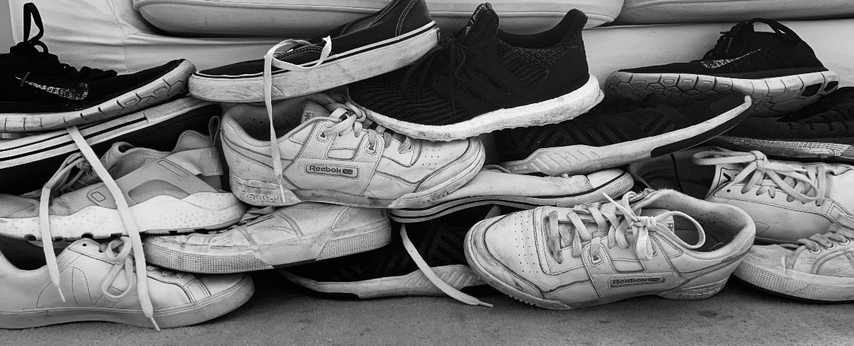 A black and white photos of a pile of trainers