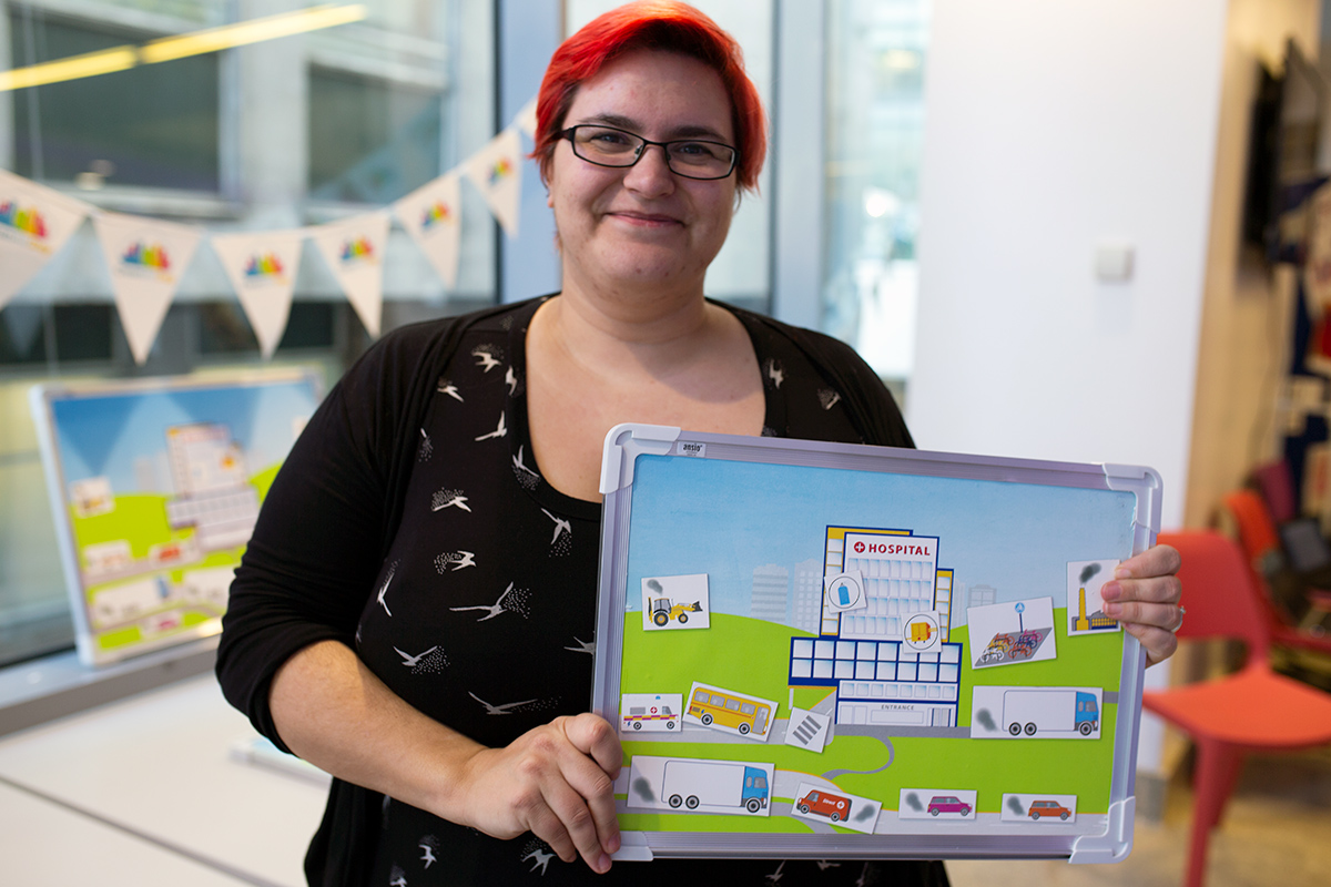 Global Action Plan staff member Clair McCowlen holds up an interactive game to show how a clean air hospital can work