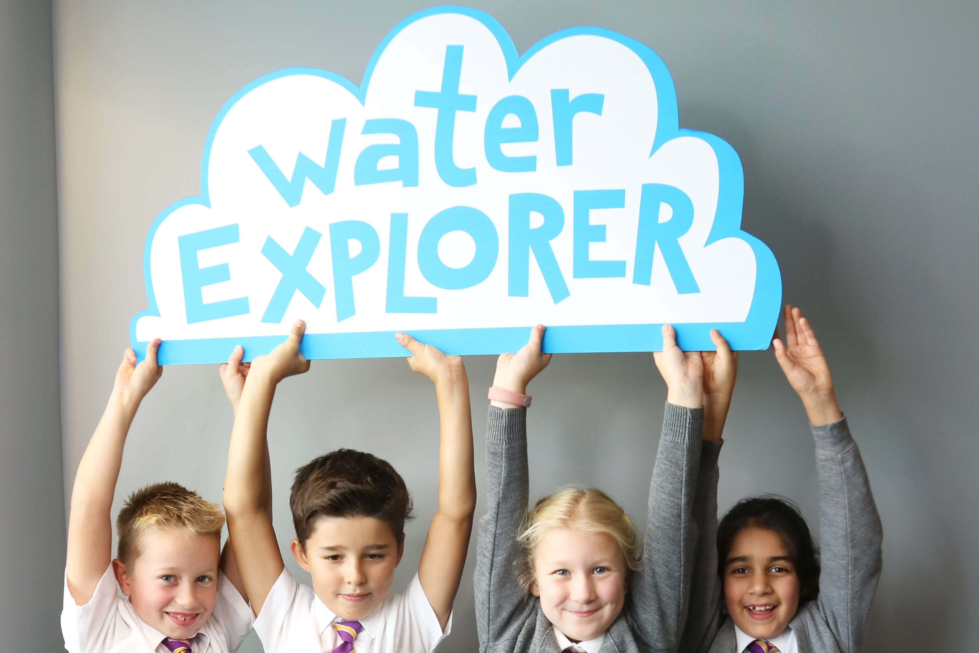 Four young school children hold up a sign saying Water Explorer