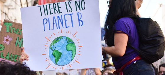 "young people at a climate strike. A poster showing the earth with the slogan ""there is no planet b"" is being held up."