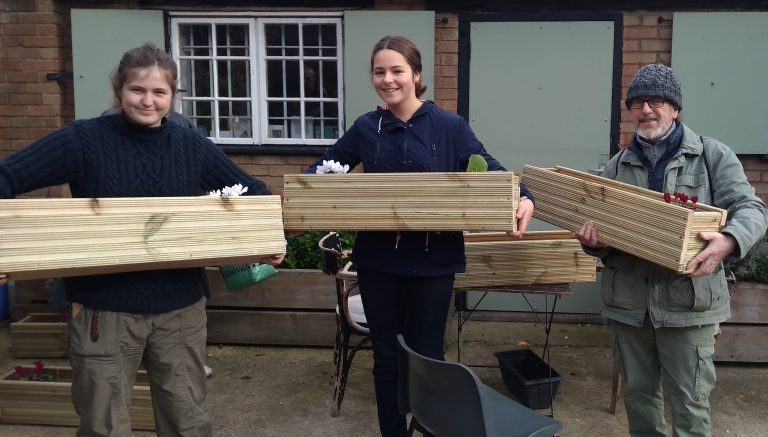 Three people holding wooden planters