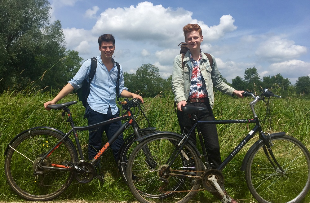 Two young men standing next to their bikes in a field.